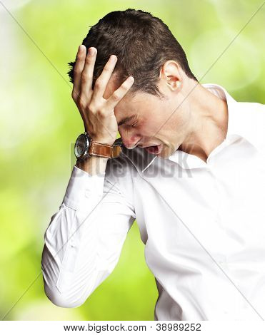 Angry young man doing frustration gesture against a nature background