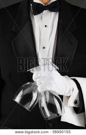 Closeup of a waiter in a tuxedo holding two wineglasses in front of his body. Man is unrecognizable.