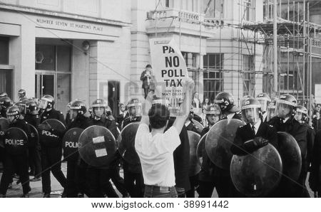 LONDON - MARCH 31: A protestor holds up a poster in front of riot police during the Poll Tax Riots on March 31, 1990 in London. The demonstration was against the unpopular Community Charge.