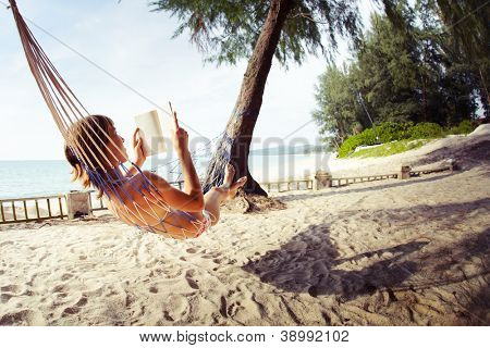 Young woman reading a book lying in a hammock on tropical sandy beach