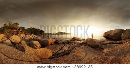 Wide angle panorama of a rocky coast of Andaman sea near Laem Sing beach at sunset light. Phuket, Thailand