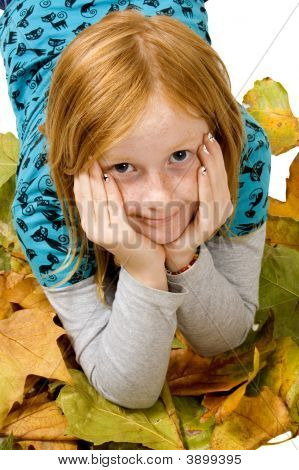 Red Head Girl Laying In Autumn Leafs