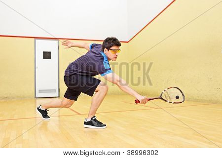 A squash player hiting a ball in a squash court
