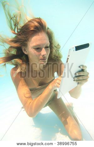 Woman using a tablet PC underwater in swimming pool