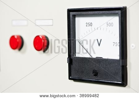 Close-up industrial electrical switch panel with red start stop button and electric voltmeter at factory