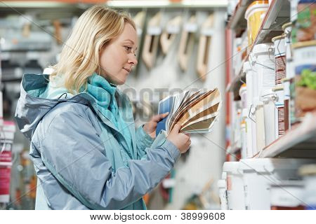 Young woman choosing paint using color samples during hardware shopping in home improvement store supermarket