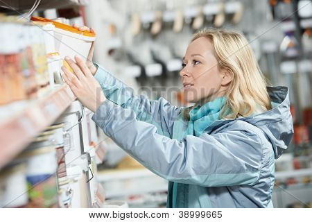 Young woman choosing color paint during hardware shopping in home improvement store supermarket