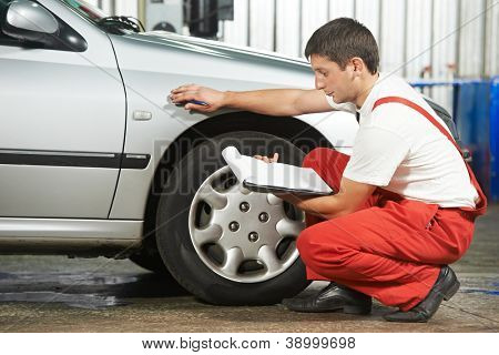 mechanic repairman inspecting car body during automobile car maintenance at auto repair shop service station