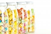 close up of four jars containing various hard candy, focus on a jar with smiley face candy
