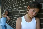 stock photo of bullying  - Portrait of sad young girl leaning on wall with child pointing at her in background representing bullying - JPG