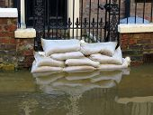 stock photo of flood  - Sandbags stacked in front of house in York flooded street - JPG
