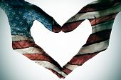 stock photo of citizenship  - man hands painted as the american flag forming a heart - JPG