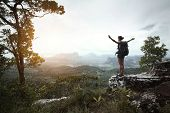 pic of wild adventure  - Young hiker with backpack standing with raised hands on a cliff - JPG
