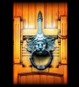Lion doorknocker on wooden elaborately carved door with glowing eyes and lights