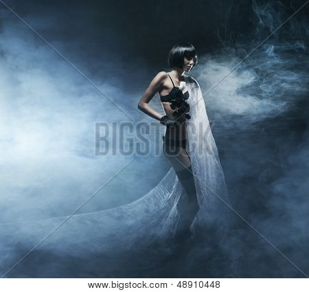 Young, beautiful and bizarre woman in fetish lingerie over the smoky background