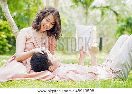 Couple relaxing in the garden, young man reading a book and lying on his girlfriend lap