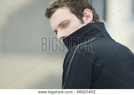 Man in sweatshirt looking over shoulder