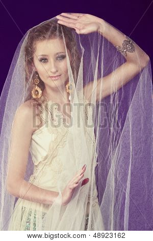 Portrait of a beautiful bride with long curly hair wearing lace dress over shorts standing under tulle veil on purple studio background