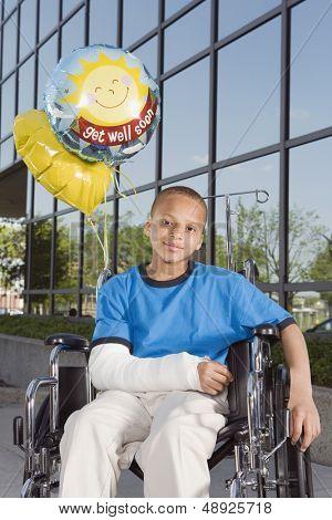 Little boy with broken arm sitting in wheelchair