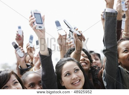 Multiethnic crowd holding up cell phones against the sky