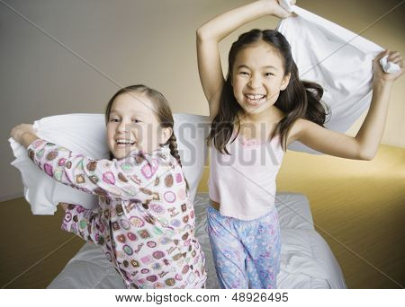 Two girls having pillow fight