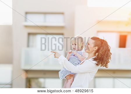 Happy Mother With Baby Standing In Front Of House Building And P