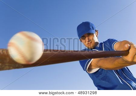Baseball player hitting the ball with a bat against clear blue sky