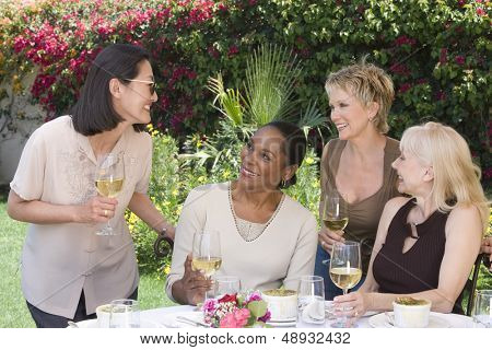 Four happy multiethnic middle aged women chatting with wine glasses at the garden party