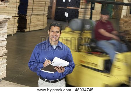 Portrait of a smiling confident man with clipboard in front of forklift in warehouse