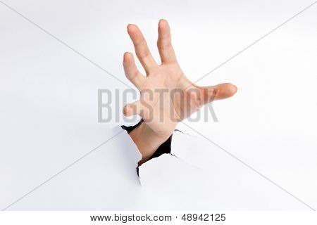Female hand reaching through torn paper sheet