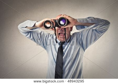 astonished businessman looking with binoculars