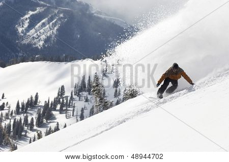 Side view of a young man snowboarding down hill