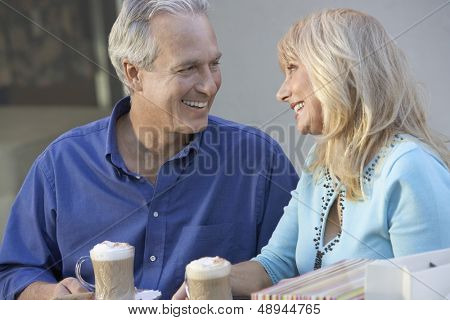 Happy and loving middle aged couple sitting at caf_ while on shopping trip