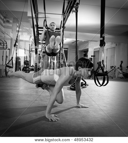 Crossfit fitness TRX training exercises at gym woman push-up and dip rings man workout