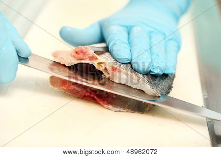 Photo of a flat fish getting sliced with a knife