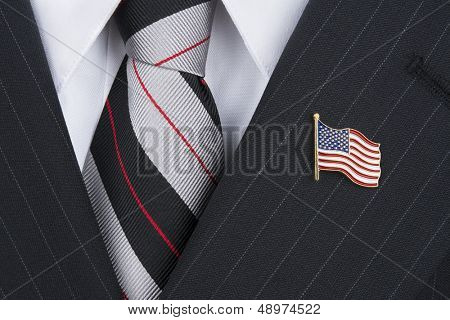 A politician wearing an American flag lapel pin symbolizes patriotism.
