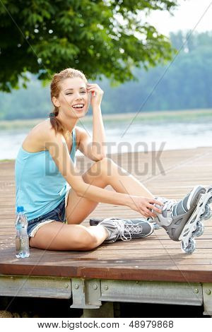 Woman skating in park. Girl going rollerblading sitting in grass putting on inline skates.