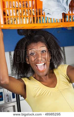Portrait of young woman screaming carrying overloaded basket of clothes in laundromat