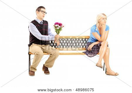 Male giving a bunch of flowers and uninterested blond female sitting on a wooden bench isolated on white background