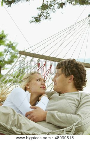 Happy dates looking at each other and smiling while lying in hammock