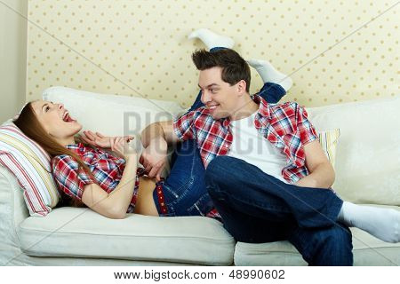 Playful guy tickling his girlfriend