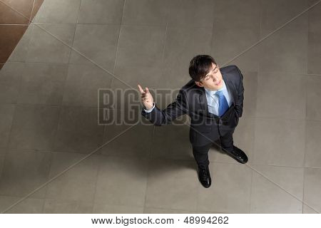 Image of young businessman with his eyes closed thumb up. Top view
