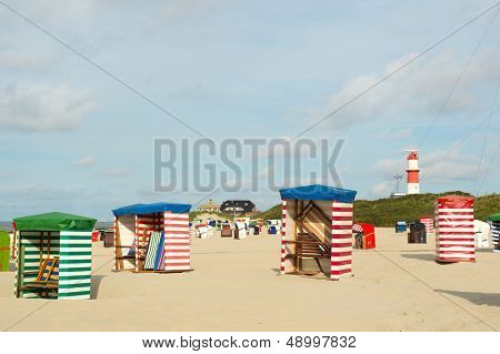 Beach of German wadden island with typical striped chair and lighthouse