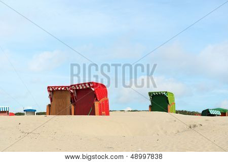 Beach of German wadden island with colorful wicker chairs