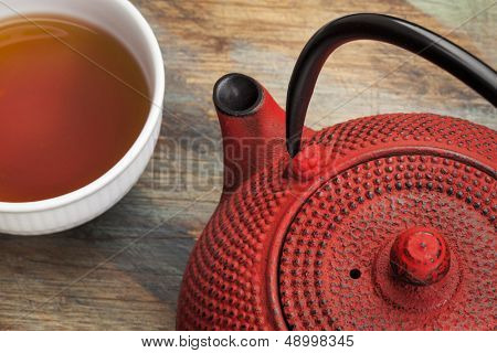red tetsubin with a cup of tea - a detail of a traditional cast iron Japenese teapot