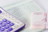 stock photo of passbook  - bank passbook with part of calculator and money close up - JPG