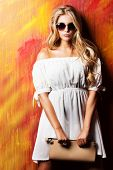 stock photo of charming  - Charming blonde girl in romantic white dress and sunglasses over vivid background - JPG