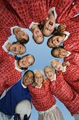Portrait of girls' soccer team forming a huddle against clear blue sky