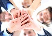 stock photo of joining  - Small group of business people joining hands - JPG