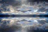 stock photo of supernatural  - A dreamlike dark blue reflected clouds background